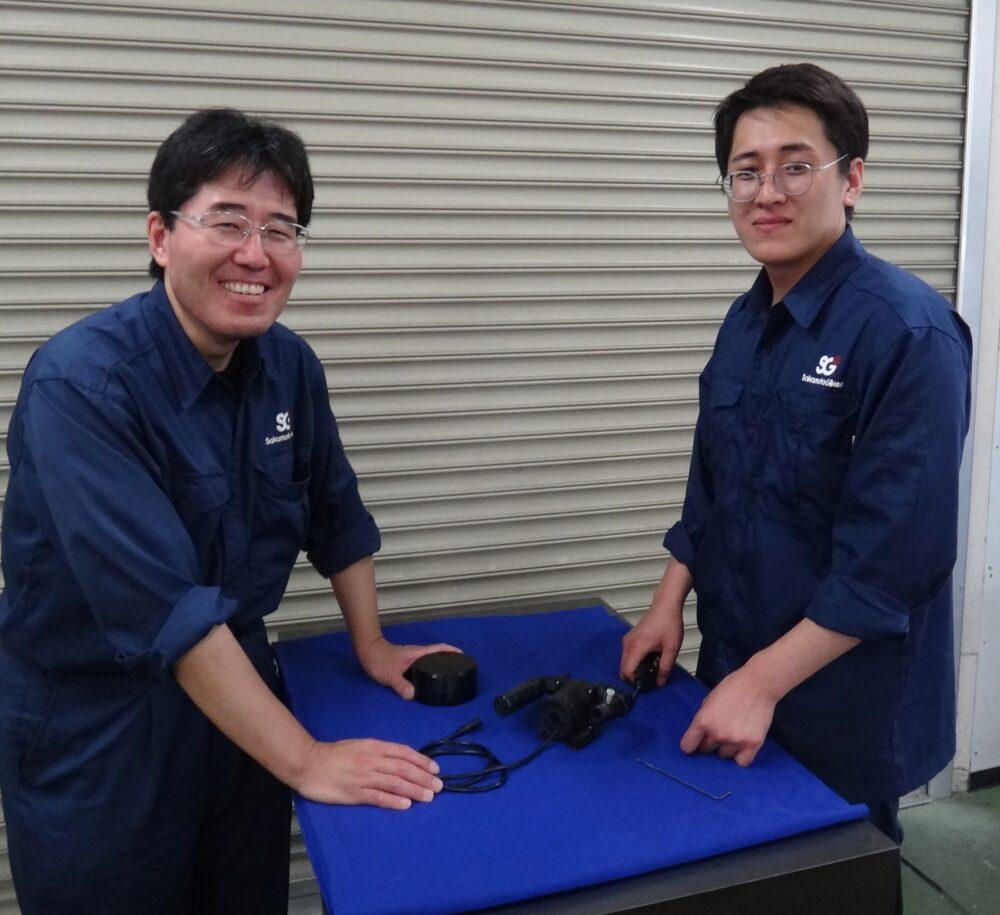 山本さんと川村さんが作業台を挟んで立っている。機器を組み立てている様子。