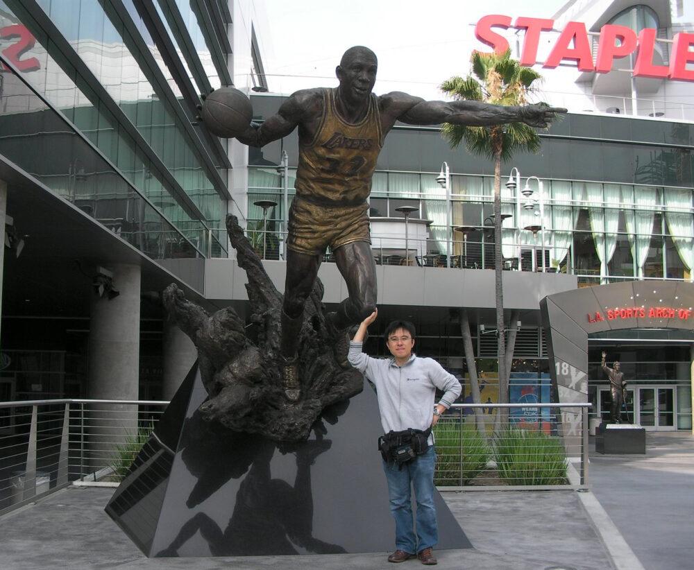 有名なバスケットボール選手の像の前でポーズをとる石川先生。