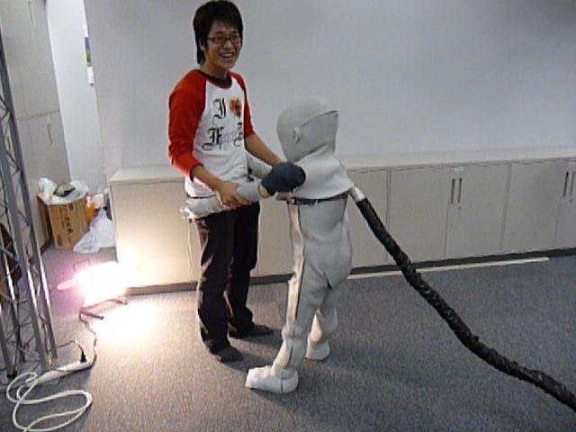 ロボットが支えられて歩く様子。