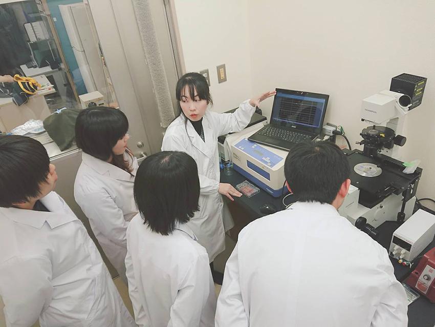 学生へ倒立顕微鏡を用いた実験についての説明する田頭先生。