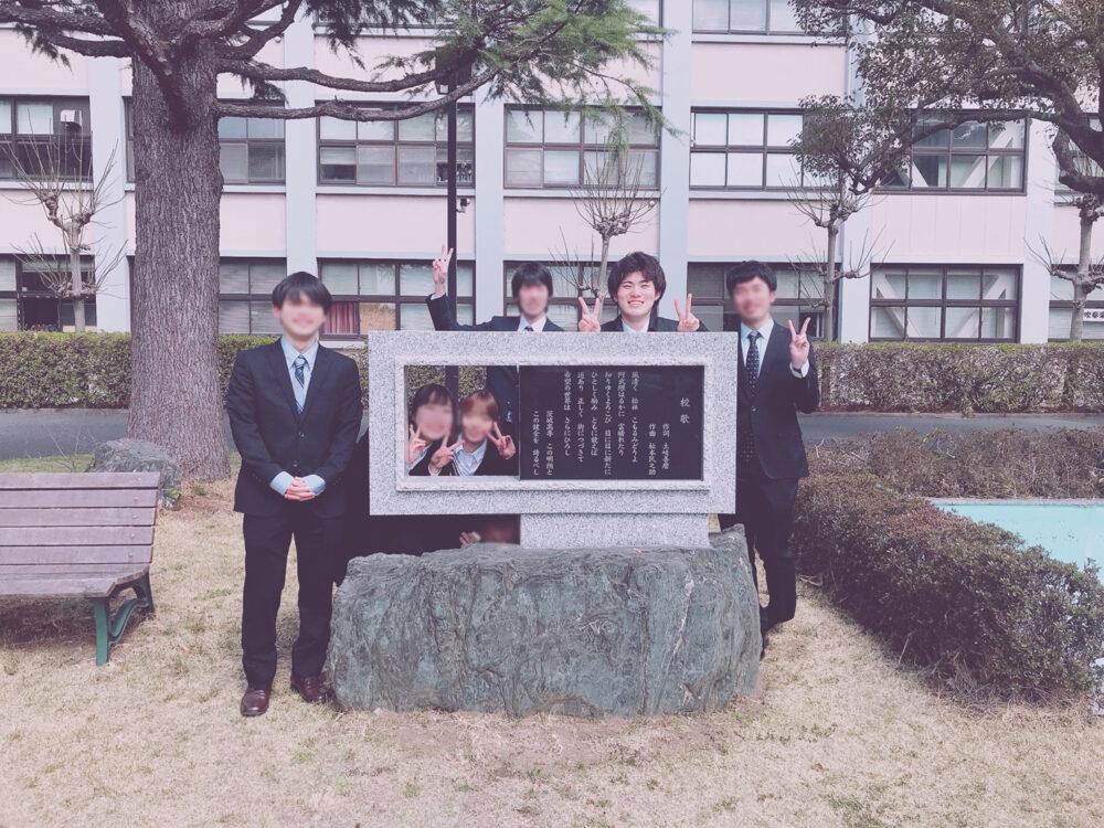 高専の学内、石碑の前で写真を撮る高久さん。