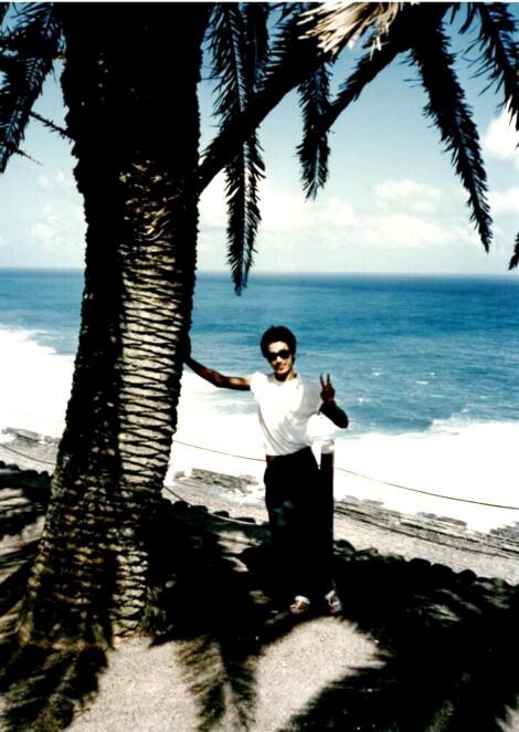 南国らしいヤシの木に右手をついて、左手でピースサインの池松先生。