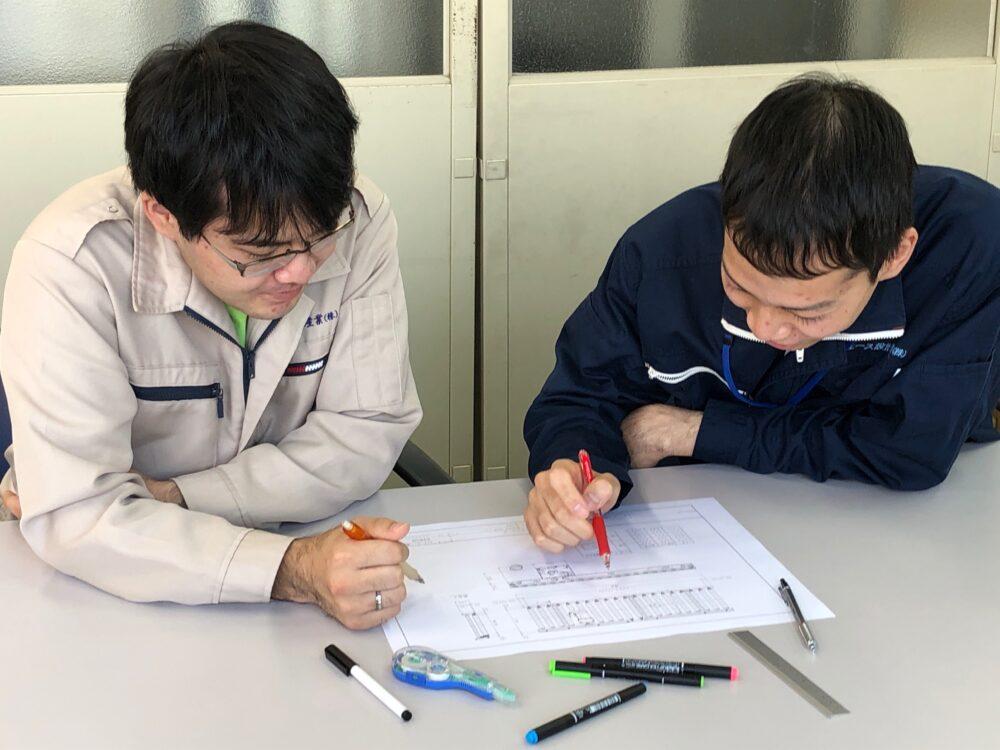 秋平さんが表に赤ペンを書き入れながら、もう一人のかたと打合せしている様子。