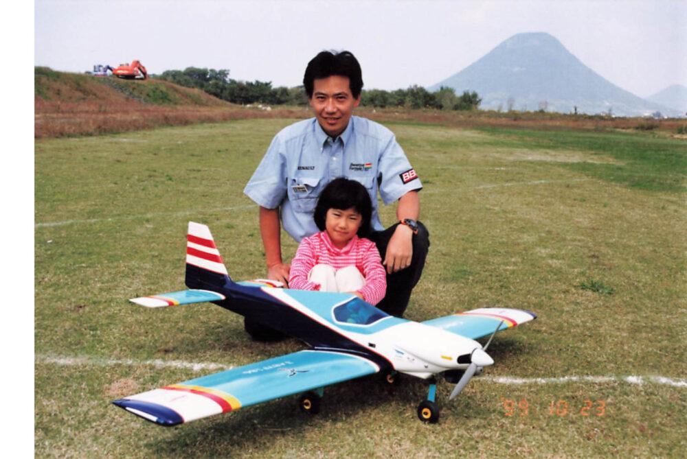 片膝を立てて座るお父さんの足元で体育座りをしている田辺先生。その手前には立派な白と水色の飛行機