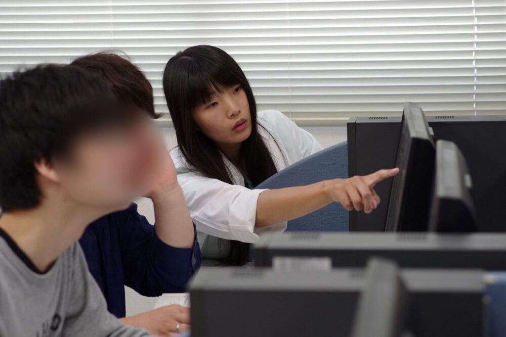 学生がPCに向かって学んでいる隣で、サポートする谷口先生