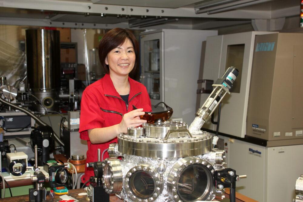 先生よりも一回り二回り大きな金属製の機械の後ろで、赤い作業着を着てはにかむ大島先生