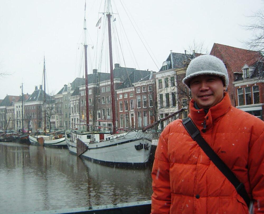 寒そうな白く曇ったなか、オランダらしい建物が並ぶ街並みを背景に、オレンジのダウンジャケットを着た笑顔の江崎先生