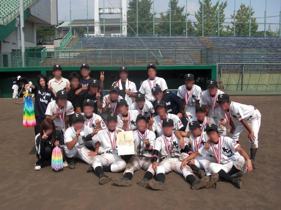 野球場での集合写真。球児たちと混じって、千羽鶴を持ってピースサインの田辺先生