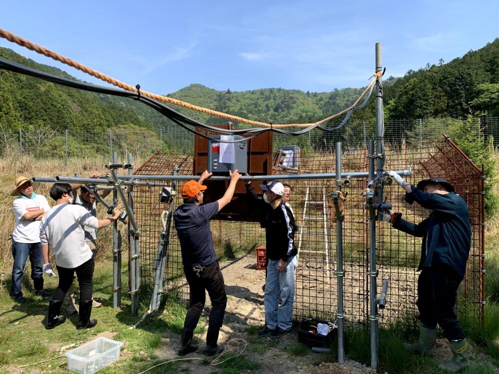 屋外の大きな装置を数人の人たちが作業する様子。