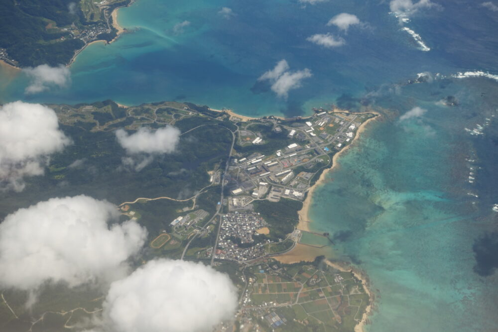 水色・青・緑のグラデーションが美しい沖縄の海と、緑豊か陸地。