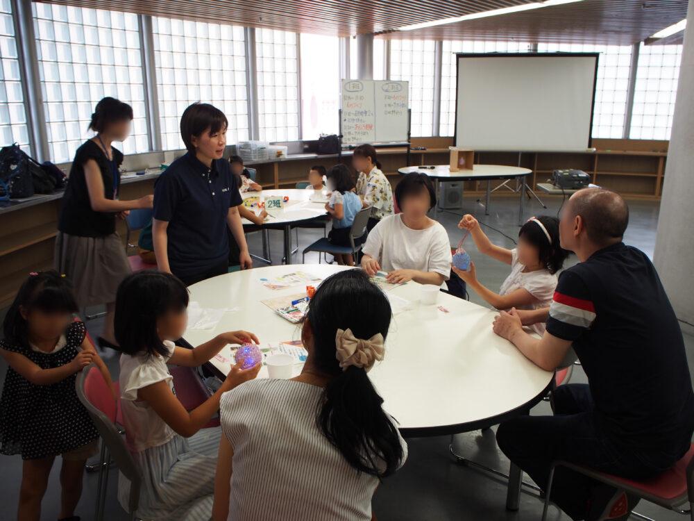 ホールのようなところで、白い楕円形のテーブルを囲んで、子どもたちと保護者が理科に親しんでいる