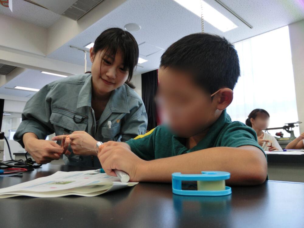 小学生に寄り添って、ものづくりを教えている田辺先生。とても優しそうな笑顔