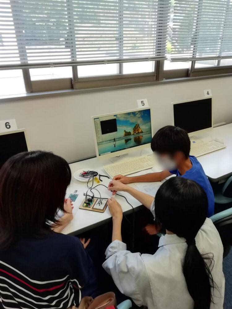 PCを前に座る子どもと、あたたかく見守る保護者との間で、しゃがんで子どもにレクチャーする谷口先生