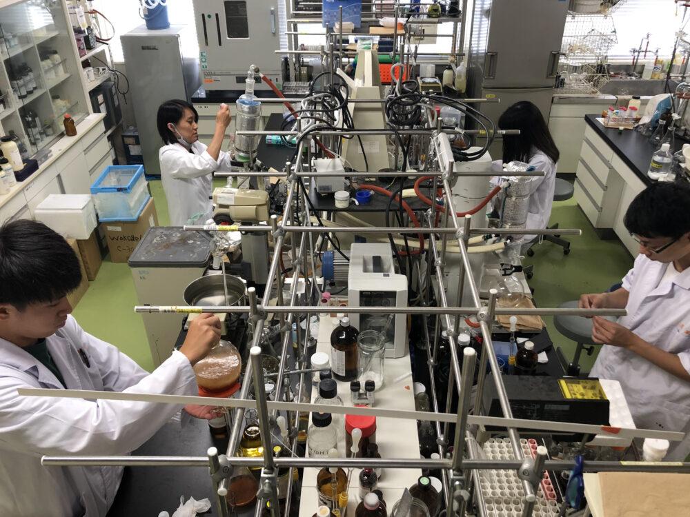 研究室の大半を占める機器類の中で、学生4名が研究している様子