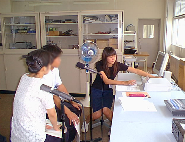 マイクや機材などがある室内で、学生さんたちに説明している様子