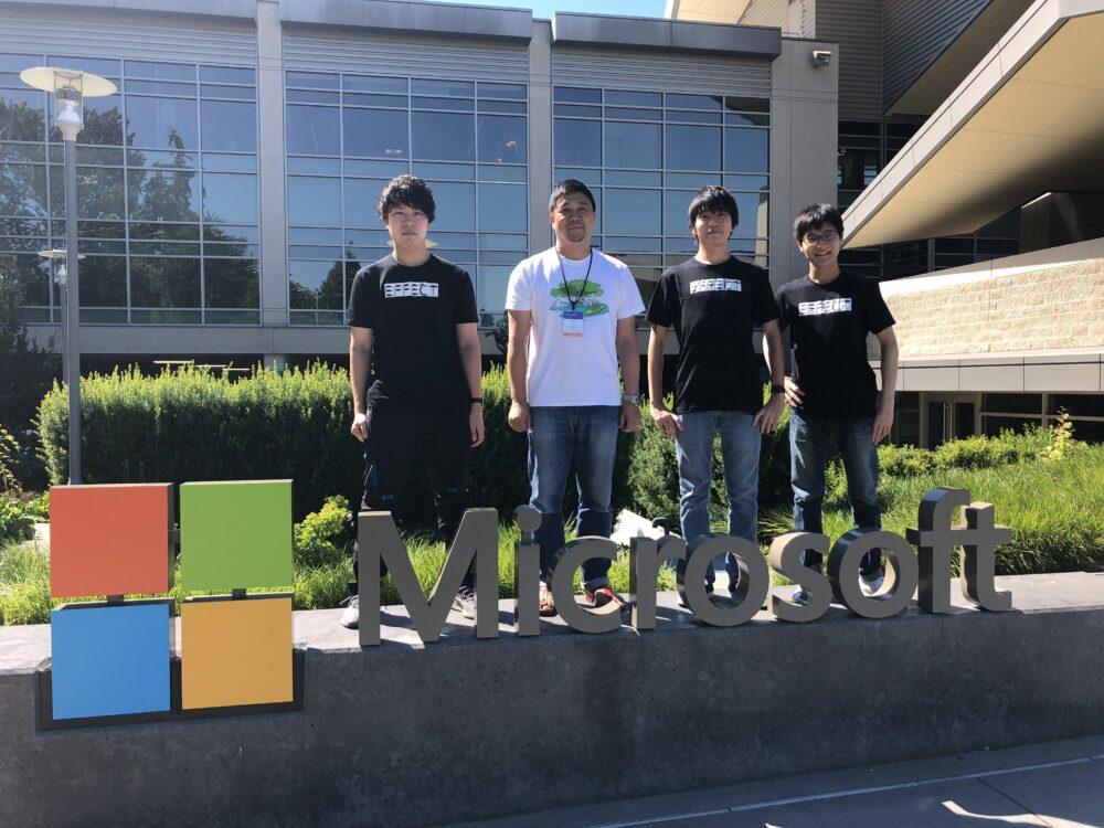 マイクロソフトの社名版とともに学生4人が集合写真。