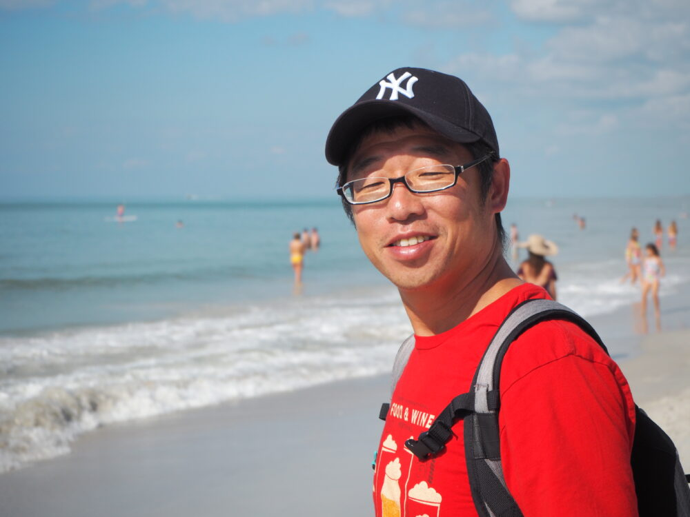 さわやかなブルーの、空と海との境目が分からないような浜辺を背景に、眩しそうに眼を細める奥野先生
