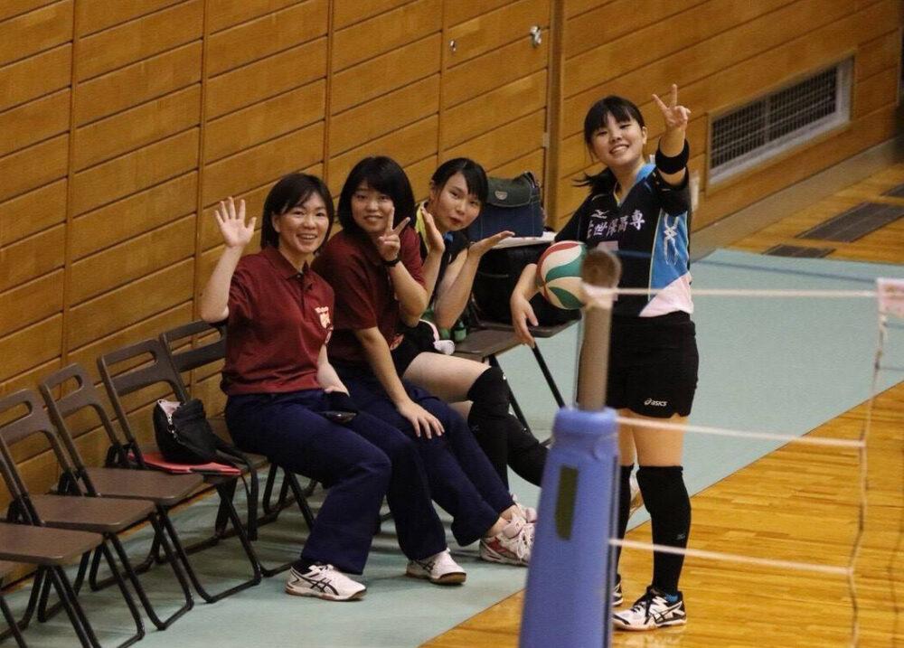 屋内のバレー場の椅子から、観覧席のカメラに向かって手を振る学生さんたちと大島先生