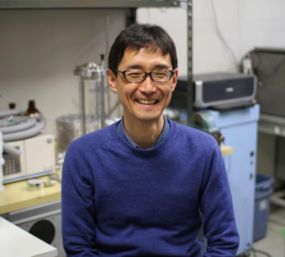 研究室の、たくさんの機材を背景に、紺色の服を着て黒縁の眼鏡を掛けて笑う谷先生