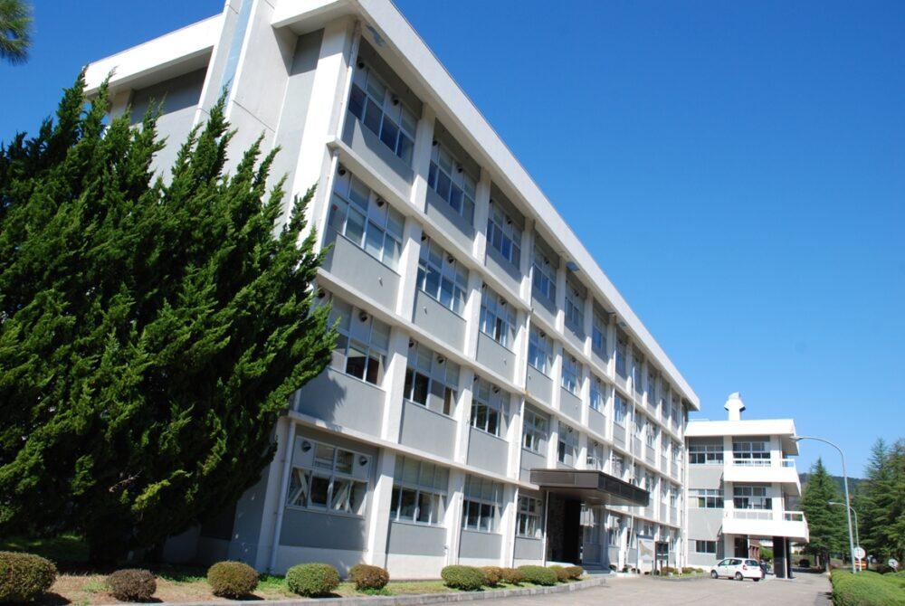 青い空、緑の木々に、4階建ての白い校舎が映える、舞鶴高専校舎