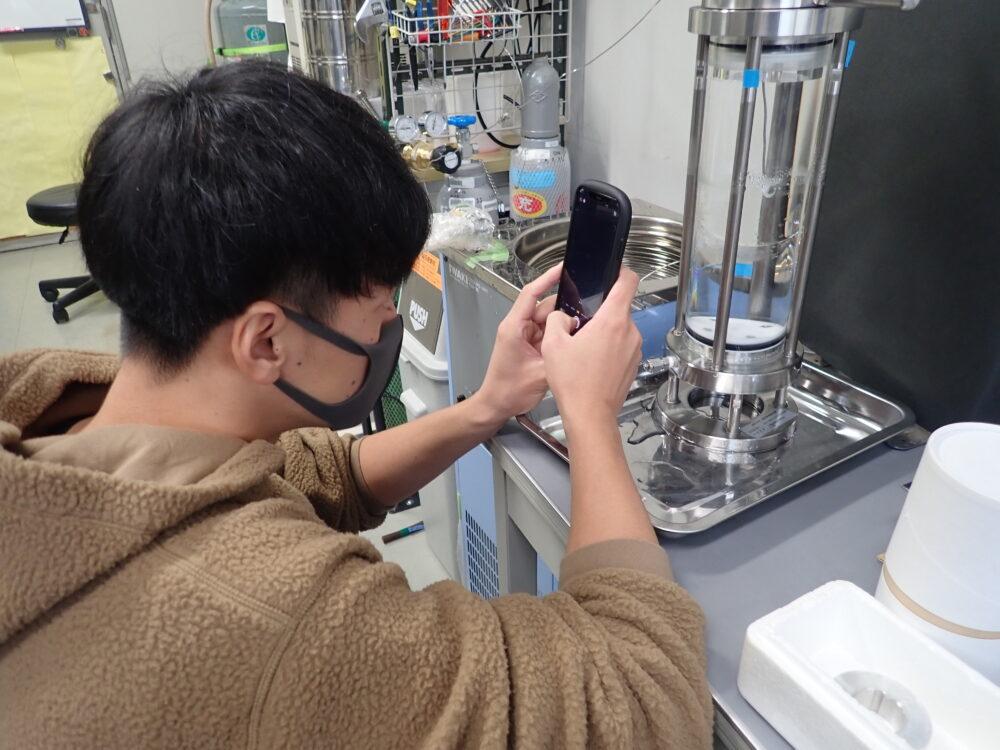 学生が圧力容器に向かってスマートフォンをかざしている(実験中)