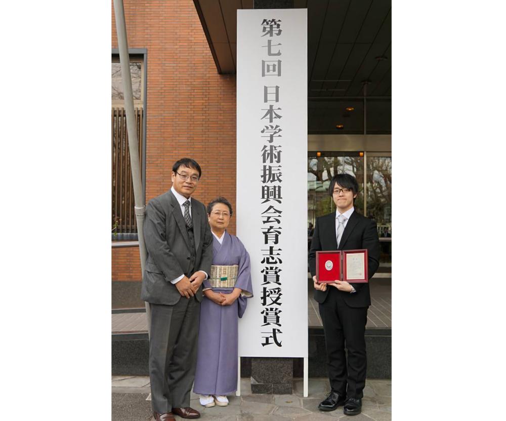「第7回 日本学術振興会育志賞授賞式」の看板の前で、ご両親とともに