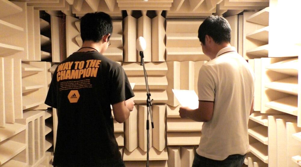 四方を凸凹した壁に囲まれた無響室で、音声の収録実験をする様子