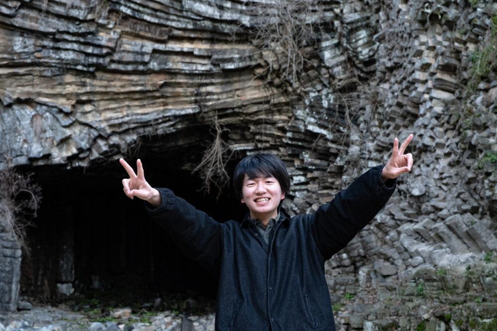 観光名所の岩場の前で両手でピースして笑う嶋田さん