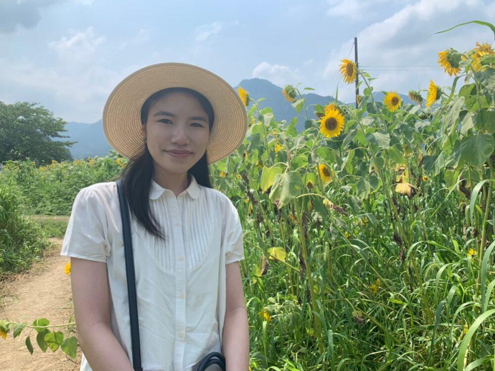 夏空のもと、ひまわりがたくさん咲き誇るなか、さわやかな白のブラウスと麦わら帽子をかぶってほほ笑む横山さん
