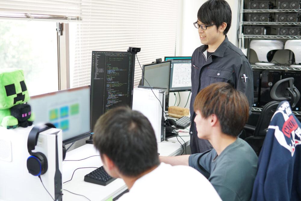 学生がPCを操作しているのを暖かくみまもる作業着姿の北村先生
