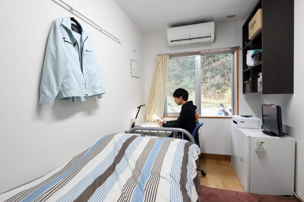 寮の1人部屋を写した写真。奥に腰壁窓があり、デスク、ベッド、逆サイドに棚などがある