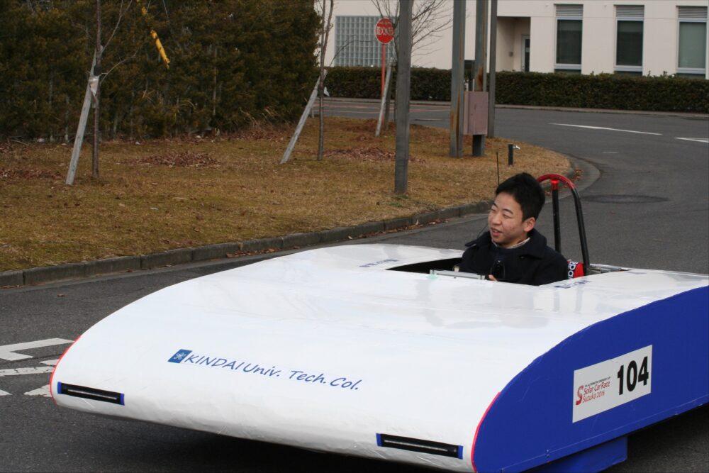高専校内の道路で、未来的なかたちのソーラーカー(白色に、側面が青色)を操縦する木村さん