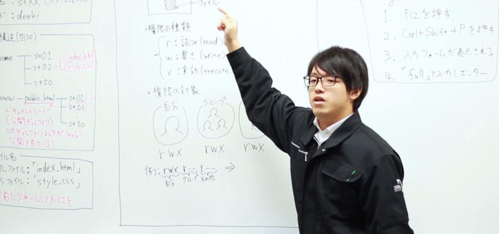 作業着姿の北村先生。ホワイトボードに書いた、実験の説明をしている