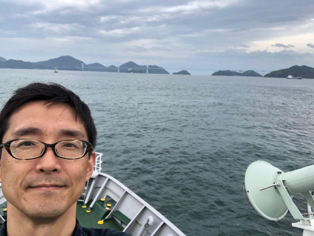 海上で、船の上で谷先生の自撮り。背景には山々と橋が。