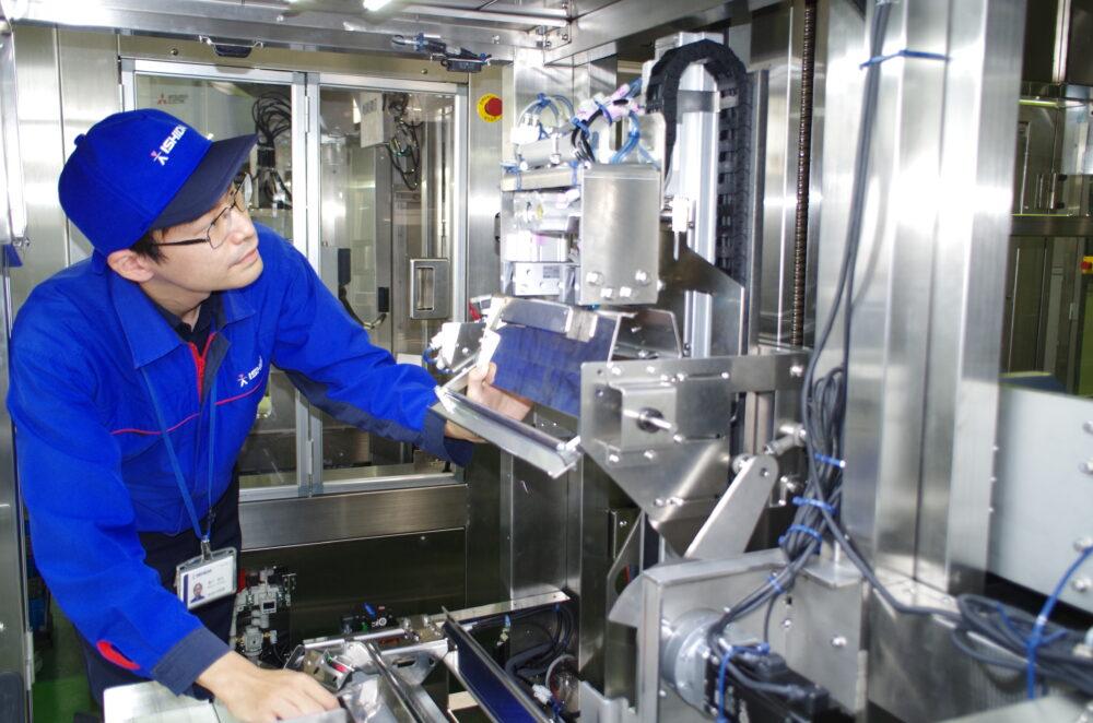 作業着とおそろいのキャップをかぶって、機器の動作確認をする黒川さん